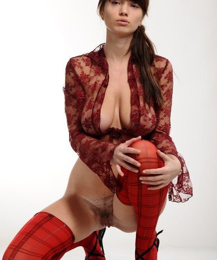 Mr Big brunette with spacious swollen breasts and sexy legs not far from red thigh-high stockings and stiletto heels.